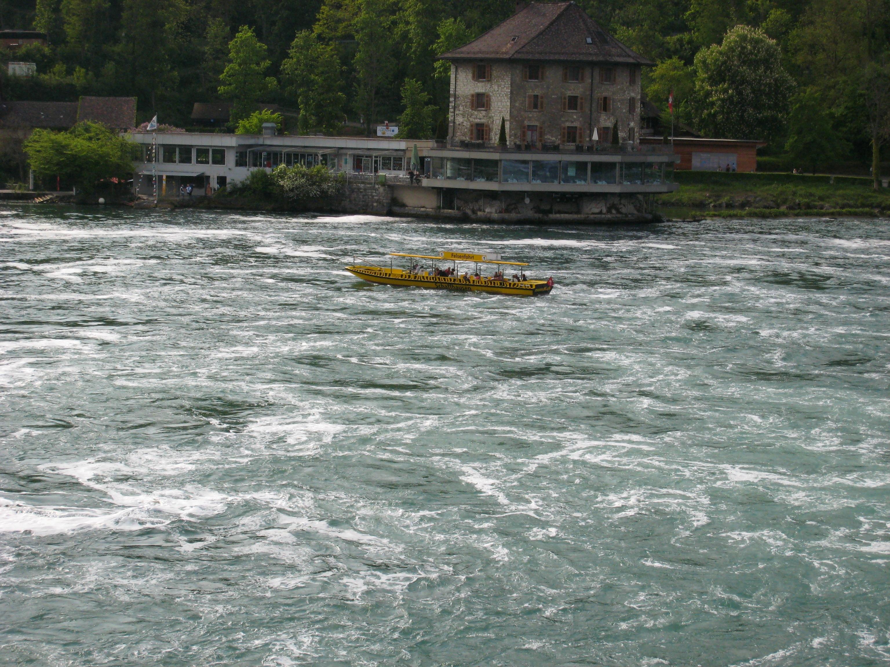 Лодка подвозит туристов к центру водопада